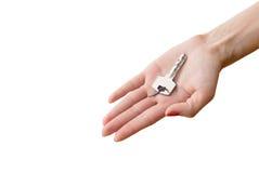 De hand die van vrouwen sleutel van huis geeft Stock Fotografie