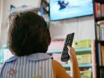 De hand die van weinig Aziatische baby een televisieafstandsbediening houden, terwijl thuis het letten van op het stock afbeelding