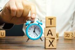 De hand die van de zakenman een klok houden dichtbij de houten blokken met de woordbelasting Tijd om belastingen te betalen Het c stock foto