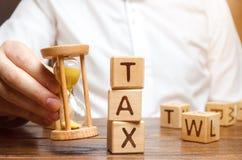 De hand die van de zakenman een zandloper houden dichtbij de houten blokken met de woordbelasting Tijd om belastingen te betalen  royalty-vrije stock afbeelding