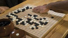 De hand die zwart-witte steenstukken op Chinees gaat of Weiqi-spelraad spelen Binnenactiviteit met kunstmatig licht Royalty-vrije Stock Foto