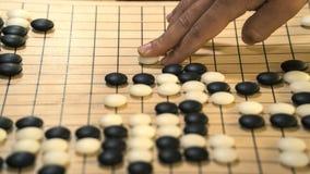 De hand die zwart-witte steenstukken op Chinees gaat of Weiqi-spelraad spelen Binnenactiviteit met kunstmatig licht stock afbeelding