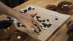 De hand die zwart-witte steenstukken op Chinees gaat of Weiqi-spelraad spelen Binnenactiviteit met kunstmatig licht royalty-vrije stock fotografie