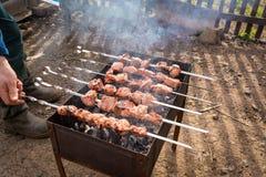 De hand draait de vleespen met vlees bij de grill Royalty-vrije Stock Foto's