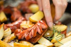 De hand, een houten spatel giet een hoog-calorie en een vettig diner royalty-vrije stock foto