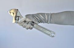 De hand en de moersleutel van de vrouw stock afbeeldingen