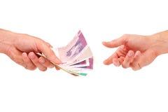 De hand geeft geld aan een andere stock afbeelding
