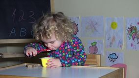 De hand geeft leuk meisjeyoghurt en brood en het begin van het peuterkind om te eten stock footage