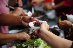 De hand geeft voedsel aan handen van een bedelaar royalty-vrije stock foto
