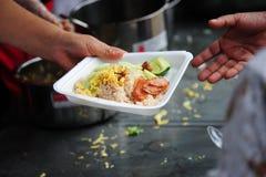 De hand geeft voedsel aan handen van een bedelaar stock afbeeldingen