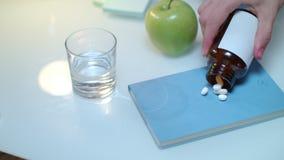 De hand giet tablet en capsules van fles op lijst Gezond geneeskundeconcept stock video