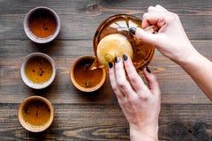 De hand giet de thee van theepot in koppen Donkere houten hoogste mening als achtergrond Stock Foto's
