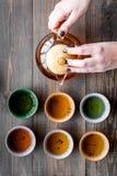 De hand giet de thee van theepot in koppen Donkere houten hoogste mening als achtergrond Stock Foto