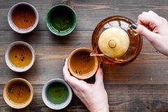 De hand giet de thee van theepot in koppen Donkere houten hoogste mening als achtergrond Royalty-vrije Stock Afbeeldingen