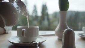 De hand gietende melk van de vrouw in koffiekop van schotel stock footage