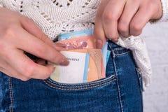 De hand haalt euro rekeningen van de zak te voorschijn Stock Foto's