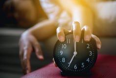 De hand haat ertoe brengend beklemtoonde ontwaken vroeg, Wijfje uitrekt haar hand aan bellend alarm om wekker uit te zetten stock foto's