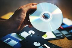 De hand houdt CD schijfachtergrond met floppy op de lijst stock foto's