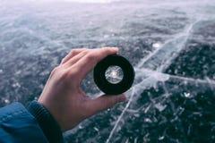 De hand houdt de cameralens op de achtergrond van het bevroren Meer stock afbeelding