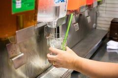 De hand houdt een glas, die het water van het drinken van automaat in het restaurant duwen stock afbeeldingen
