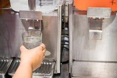 De hand houdt een glas, die het water van het drinken van automaat in het restaurant duwen stock foto's