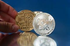 De hand houdt een gouden muntstuk bitcoin op een blauwe achtergrond Dichtbij is een zilveren muntstuk bitcoin op de rand Royalty-vrije Stock Afbeeldingen