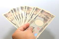 De hand houdt een 10000 Japanse munt, rekeningsyen in een Portefeuille van de krokodiltextuur, op witte achtergrond, een exemplaa Royalty-vrije Stock Afbeeldingen