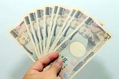 De hand houdt een 10000 Japanse munt, rekeningsyen in een Portefeuille van de krokodiltextuur, op witte achtergrond, een exemplaa Royalty-vrije Stock Foto