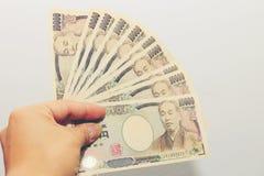 De hand houdt een 10000 Japanse munt, rekeningsyen in een Portefeuille van de krokodiltextuur, op witte achtergrond, een exemplaa royalty-vrije stock afbeelding