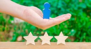 De hand houdt een menselijk cijfer en drie sterren Het concept een bedrijfsleider en een deskundige manager Succes en voltooiing  stock foto