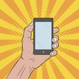 De hand houdt een mobiele telefoon Hand getrokken pop-artillustratie bij grappige zonnestraalachtergrond met punten halftone effe Royalty-vrije Stock Afbeeldingen