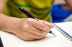 De hand houdt een pen en schrijft op een boek Royalty-vrije Stock Foto's
