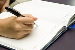 De hand houdt een pen en schrijft op een boek Stock Fotografie