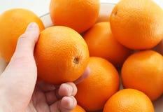 De hand houdt een sinaasappel Stock Afbeelding
