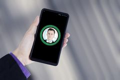De hand houdt een smartphone met gezichtsidentificatie stock fotografie