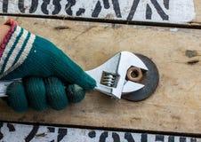 De hand houdt moersleutel en haalt de noot op houten aan Royalty-vrije Stock Foto's