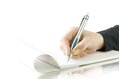 De hand houdt pen en het schrijven op het notitieboekje Royalty-vrije Stock Foto's