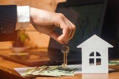 De hand houdt de sleutels aan het huis Concept onroerende goederen verkoop of huur van huisvesting, flathuur realtor royalty-vrije stock fotografie