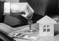 De hand houdt de sleutels aan het huis Concept onroerende goederen verkoop of huur van huisvesting, flathuur realtor zwart-wit stock afbeeldingen