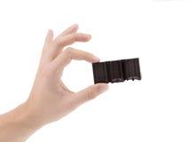 De hand houdt smakelijke hap van donkere chocolade. Stock Foto
