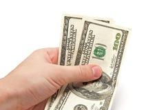 De hand houdt twee 100 dollar rekeningen Royalty-vrije Stock Foto