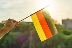 De hand houdt de vlag van Duitsland een open venster Blauwe hemel als achtergrond, silhouet van de stad, zonsondergang royalty-vrije stock afbeelding