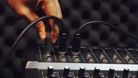 De hand iemand verbindt USB-schakelaars van microfoon op de correcte muziekmixer Het voorwerp van de mengelingsverscheidenheid in stock video