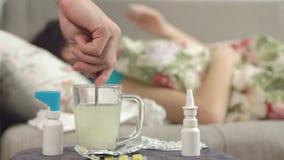 De hand kneedt de geneeskunde in een mok tegen een zieke jonge vrouw stock video