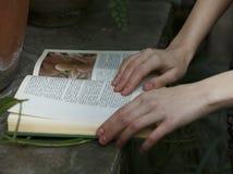 De hand ligt op een boek stock fotografie