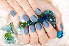 De hand met blauwe steen manicured spijkers Stock Foto