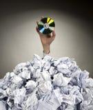 De hand met CD bereikt uit van hoop van documenten stock fotografie