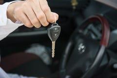 De hand met een auto sluit in auto Royalty-vrije Stock Afbeeldingen