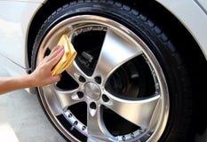 De hand met een microfiber veegt auto het oppoetsen af Royalty-vrije Stock Afbeelding