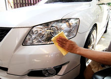 De hand met een microfiber veegt auto het oppoetsen af Stock Afbeelding